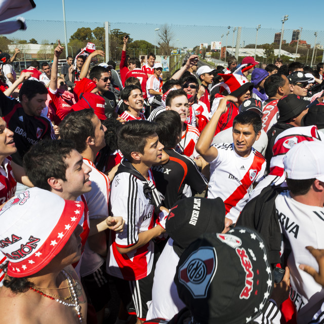 """Buenos Aires, Argentina - October 10, 2013: Supporters of the River Plate soccer team sing and dance while waiting for the doors of the stadium to open before a soccer match between the River Plate and Boca Juniors teams."" stock image"