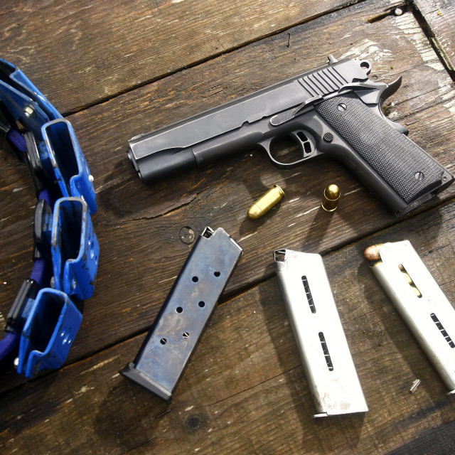 """""""Gun and bullets on a table"""" stock image"""