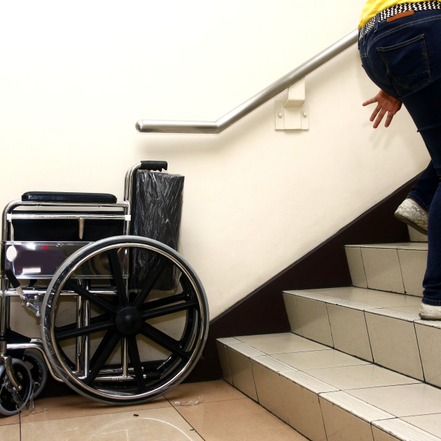 """A wheelchair, a set of staircase and a person going up the stairs."" stock image"