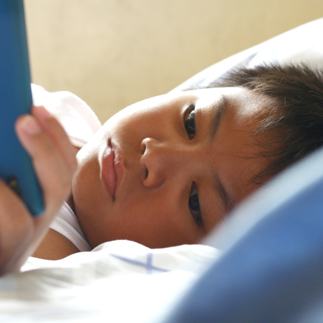 """""""Young kid watching on a smartphone"""" stock image"""
