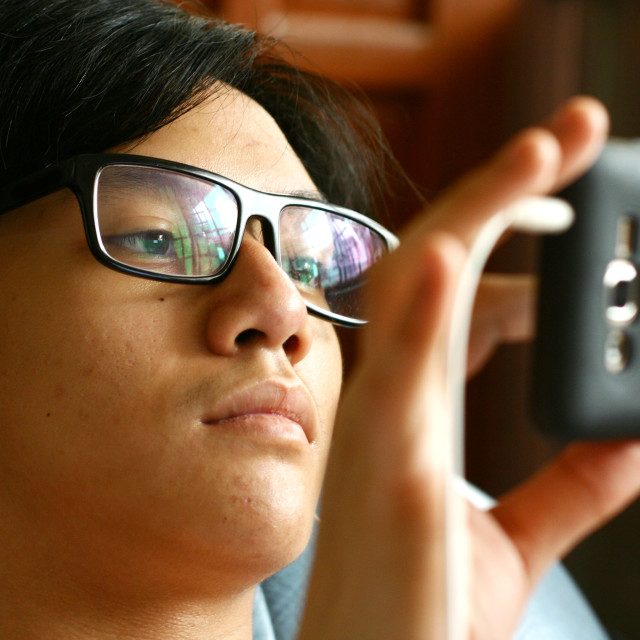"""Teenager with eyeglasses using a smartphone"" stock image"