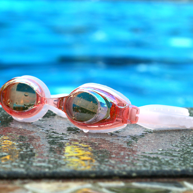 """Pair of swimming goggles beside a swimming pool"" stock image"