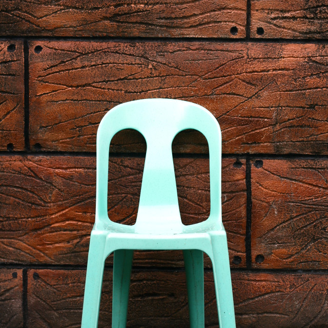 """Plastic chair and a brown wall"" stock image"