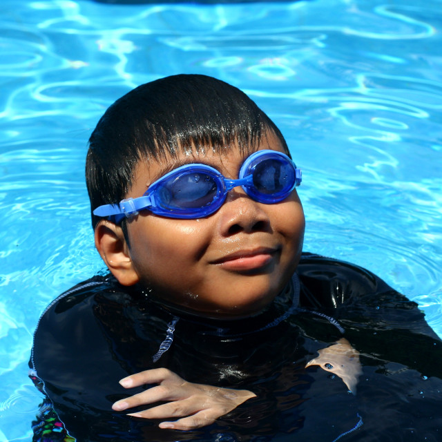 """Young kid with swimming goggles smiling while in a swimming pool."" stock image"