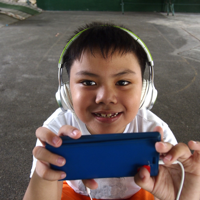 """Young kid with a smartphone and headphones"" stock image"