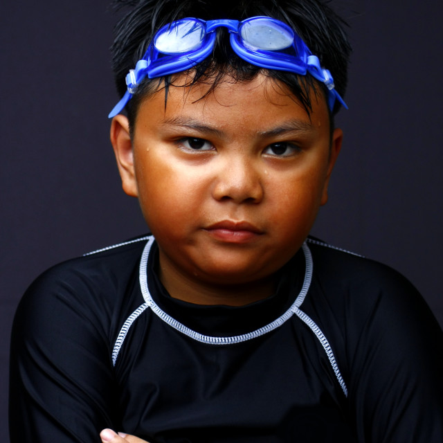 """Young swimmer kid with goggles and sun burn marks on his face"" stock image"