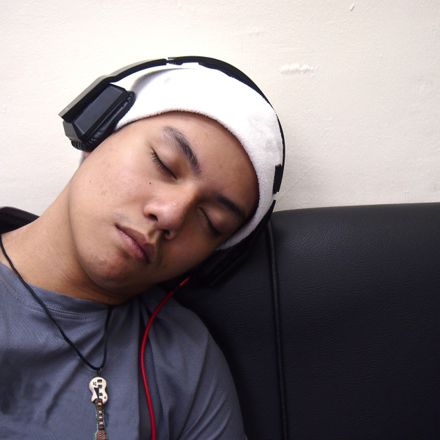 """Teenager with headphone and beany sleeping on a couch"" stock image"