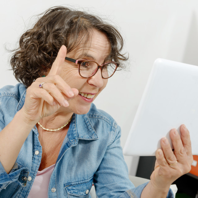 """middle-aged woman making a distant call on internet"" stock image"
