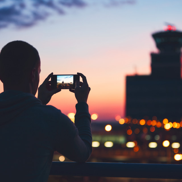 """Silhouette of the traveler with mobile phone at the airport. Air Traffic Control Tower at the amazing sunset. Prague, Czech Republic."" stock image"