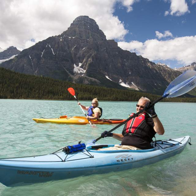 """""""A Canadian couple kayaking on Waterfowl Lake in the Canadian Rockies."""" stock image"""