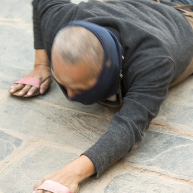 """""""A Nepalese Buddist prostrating himself around the Buddha Stoupa in Kathmandu,..."""" stock image"""