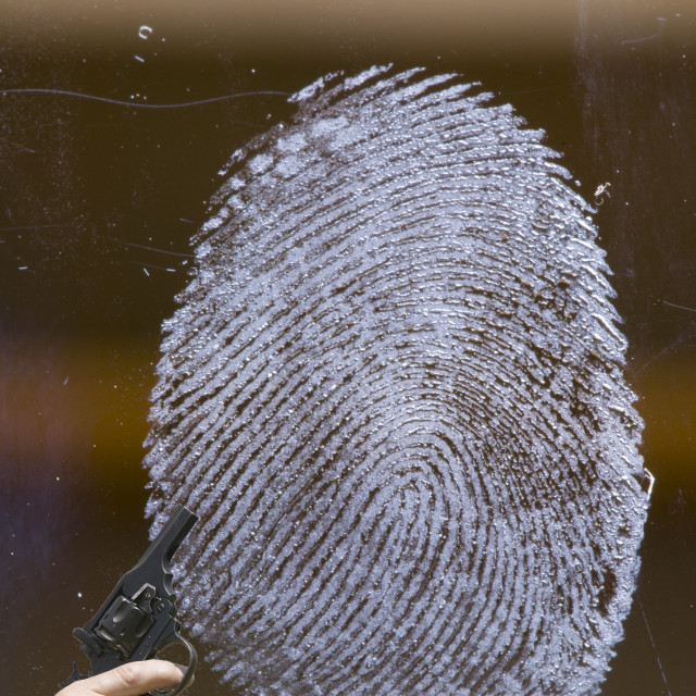 """a fingerprint on glass, with an illegal hand gun."" stock image"