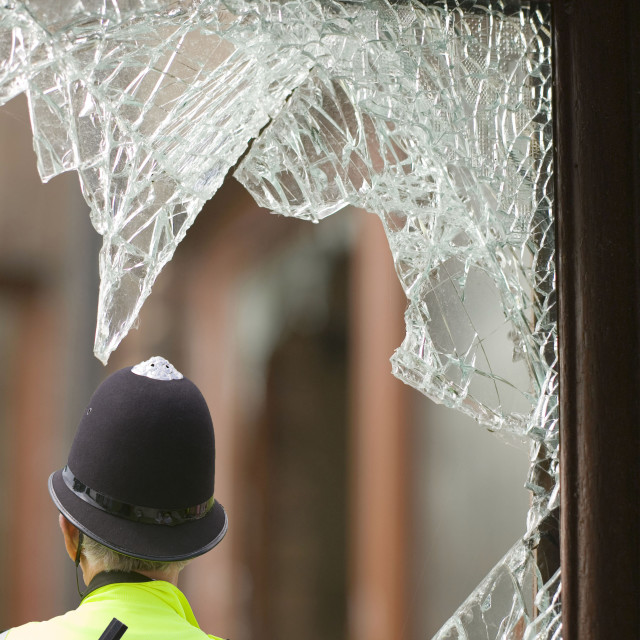"""""""A policmean outside a house break in in Carlisle Cumbria UK and a hand gun."""" stock image"""