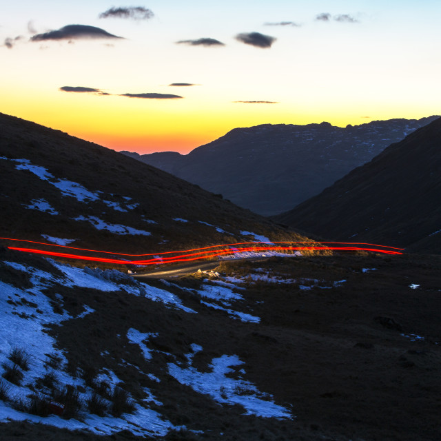 """""""Car lights over Wrynose Pass at sunset, Lake District, UK."""" stock image"""