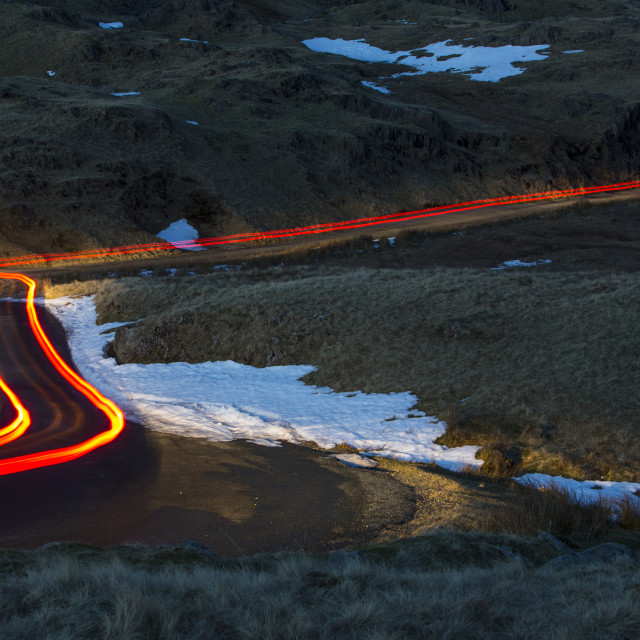 """""""Car lights over Wrynose Pass at dusk, Lake District, UK."""" stock image"""