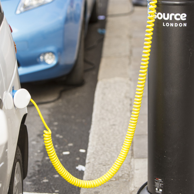 """""""An electric car at a pavement recharging station in London."""" stock image"""