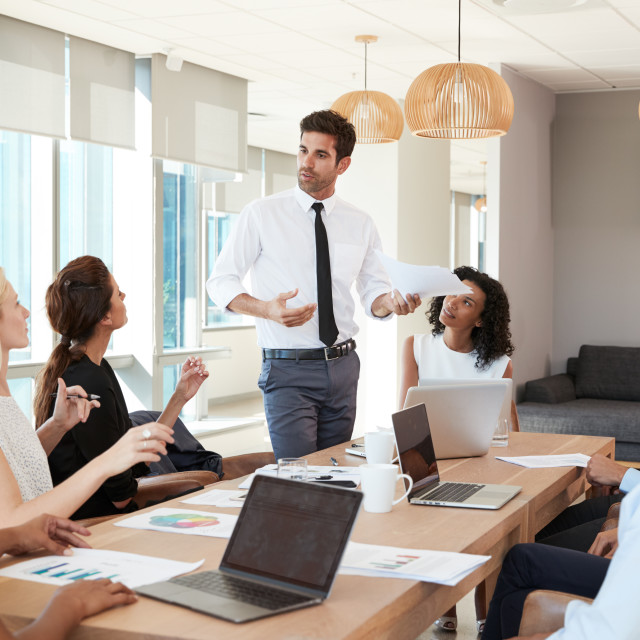 """Businessman Leads Meeting Around Table Shot Through Door"" stock image"
