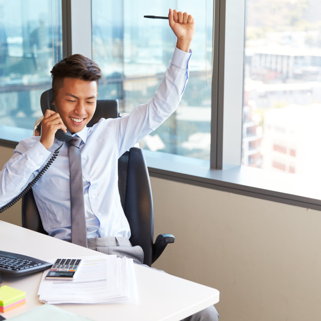 """""""Celebrating Businessman Making Phone Call At Desk In Office"""" stock image"""
