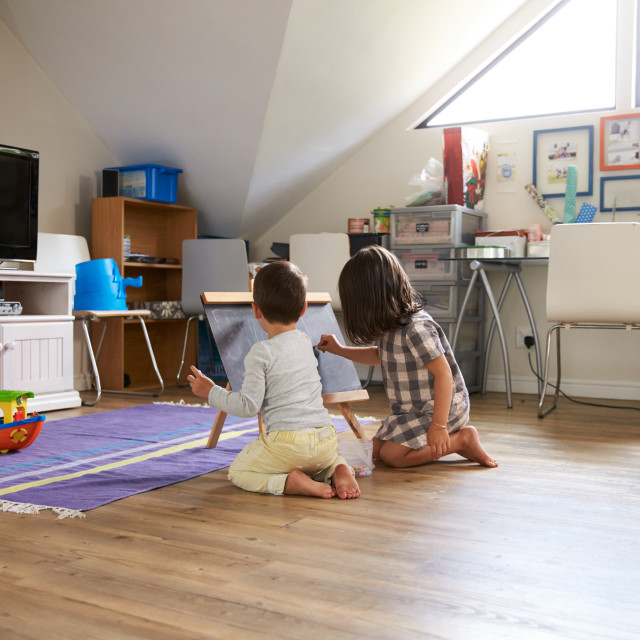 """Boy And Girl Drawing On Chalkboard In Playroom"" stock image"