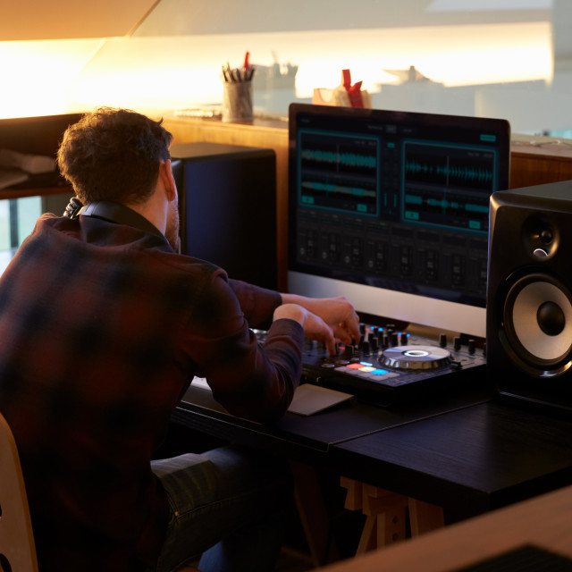 """""""Man Composing Music on Computer in Bedroom"""" stock image"""