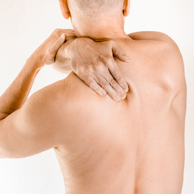 """Man suffering of thoracic vertebrae or trapezius muscle pain"" stock image"