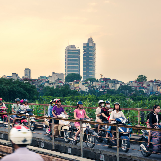 """""""HANOI, VIETNAM - People on motorbikes crossing the Long Bien bridge in Hanoi, which connects two parts of the city"""" stock image"""