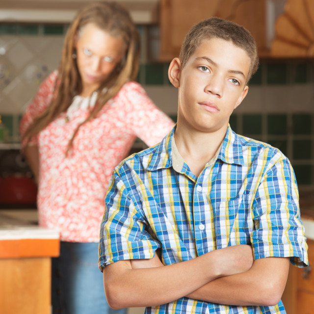 """""""Mother stands with hands on hips in kitchen behind frustrated son"""" stock image"""