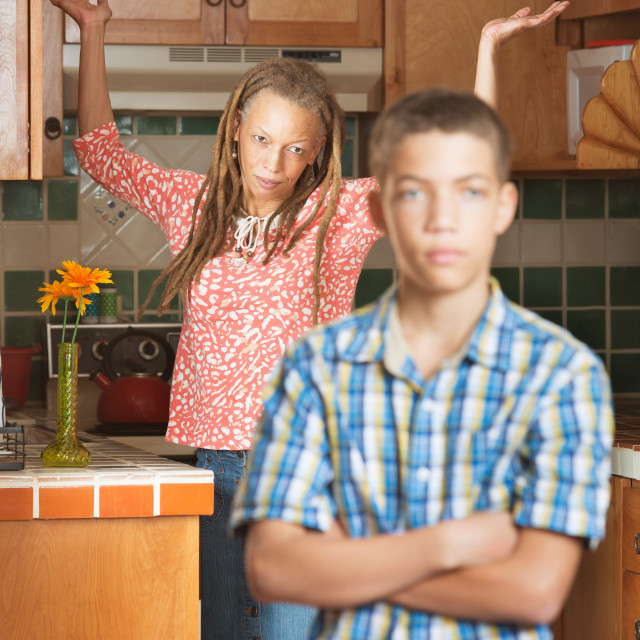 """""""Frustrated teen stands with arms crossed as his mother throws her hands in..."""" stock image"""