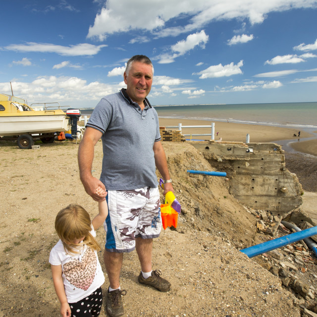 """John mincher and grand daughter stand beside smashed concrete sea defences at..."" stock image"