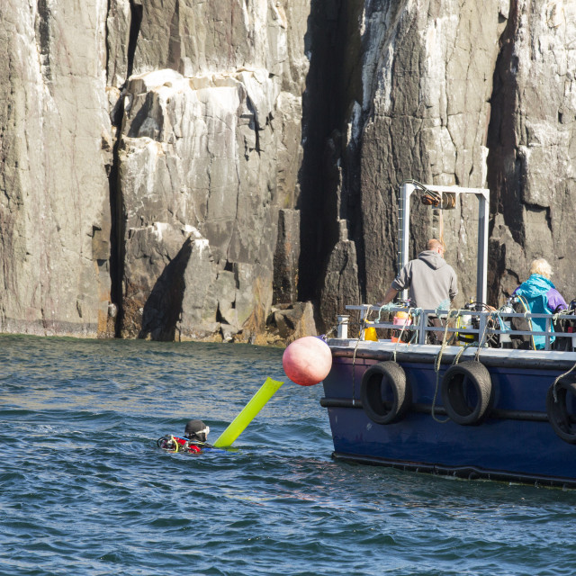 """""""A Dive boat and divers off the Farne Islands, Northumberland, UK."""" stock image"""