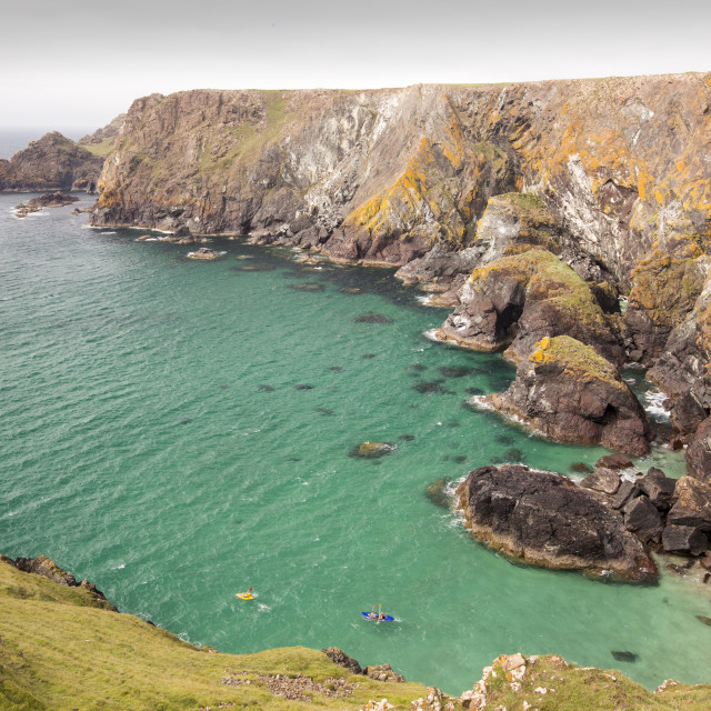 """""""Kayakers in a cove near Mullion Cove on the lizard Peninsular, Cornwall, UK."""" stock image"""