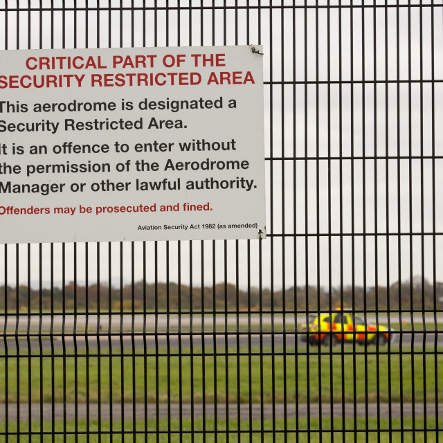 """""""Signs on security fencing at Manchester Airport, UK."""" stock image"""