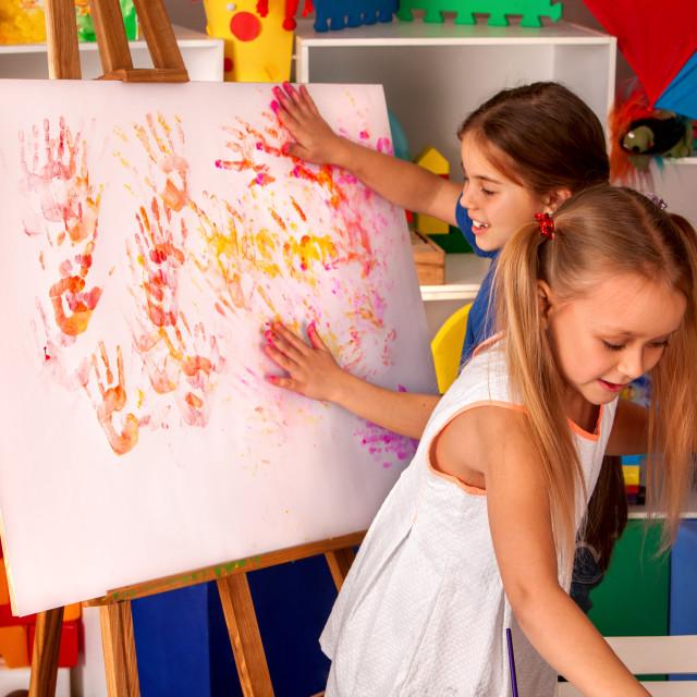 """""""Children painting finger on easel in art class."""" stock image"""