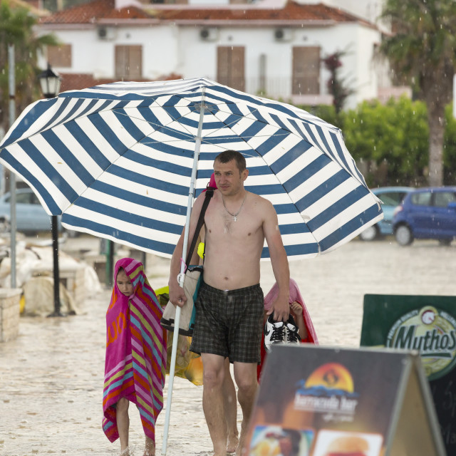 """A family use a large beach umbrella to escape torrential rain and hail from a..."" stock image"