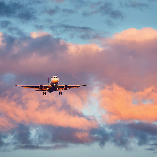 """Airplane landing at the sunset"" stock image"