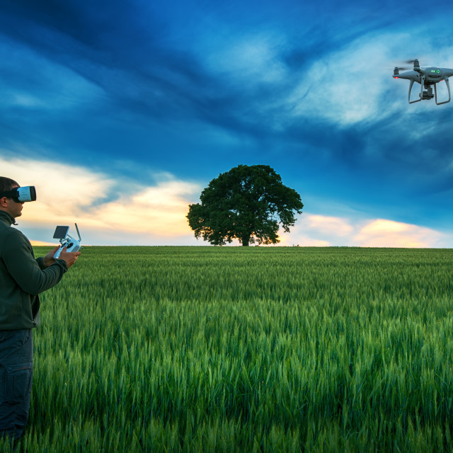 """Man with drone wearing virtual reality goggles in a field"" stock image"