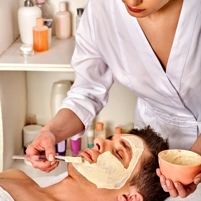 """""""Mud facial mask of woman in spa salon. Face massage ."""" stock image"""