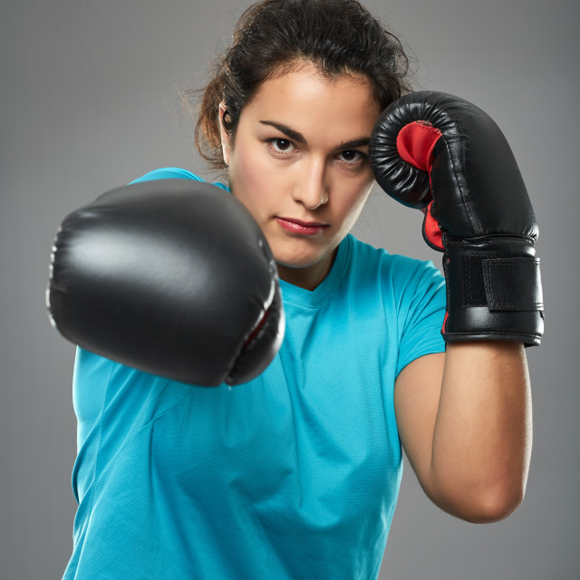 """Latino female fighter delivering a jab"" stock image"