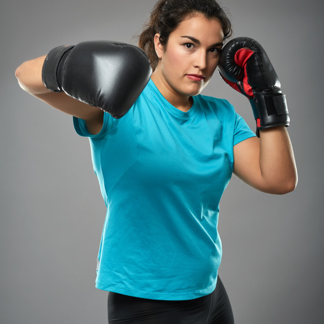 """Latino female fighter throwing a hook"" stock image"
