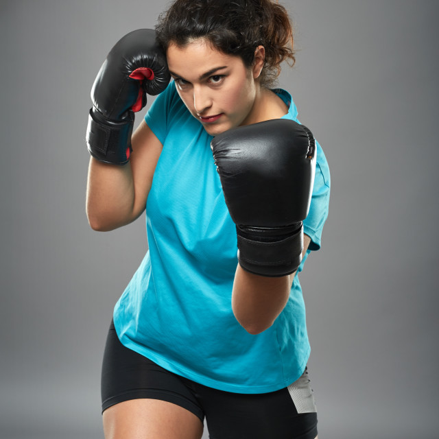"""Latino female fighter throwing an uppercut"" stock image"