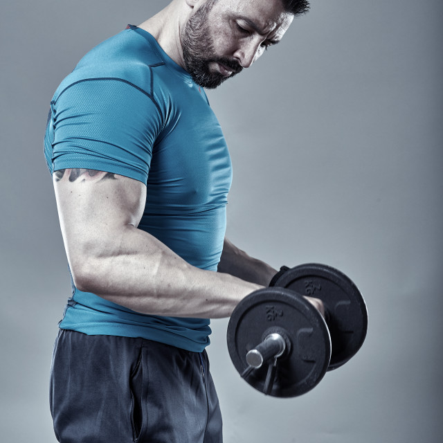 """""""Fitness trainer doing biceps workout"""" stock image"""
