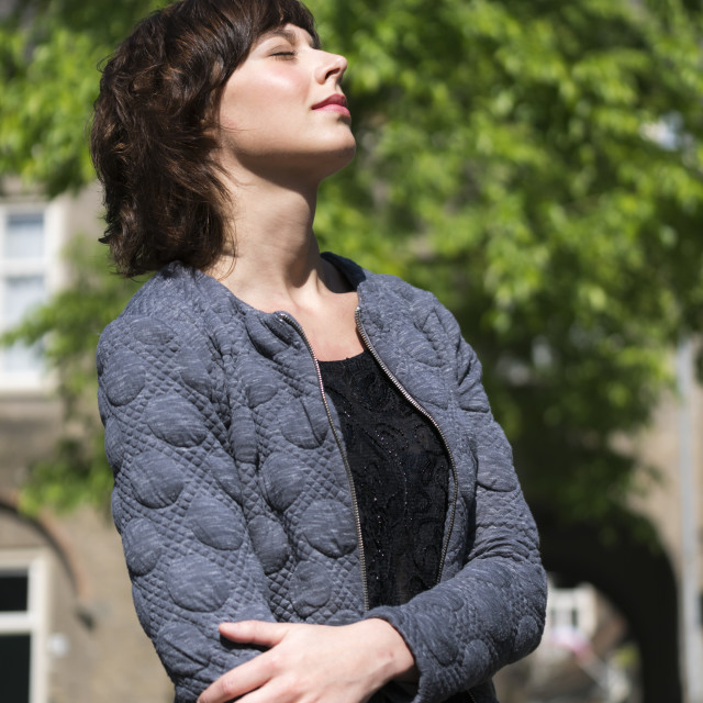 """""""Woman daydreaming in warm sunlight"""" stock image"""