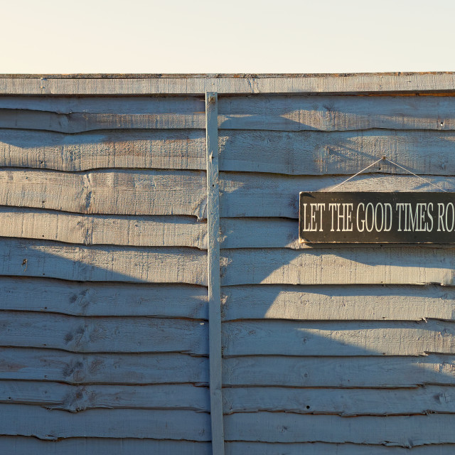 """Let The Good Times Roll Sign hanging on a fence"" stock image"