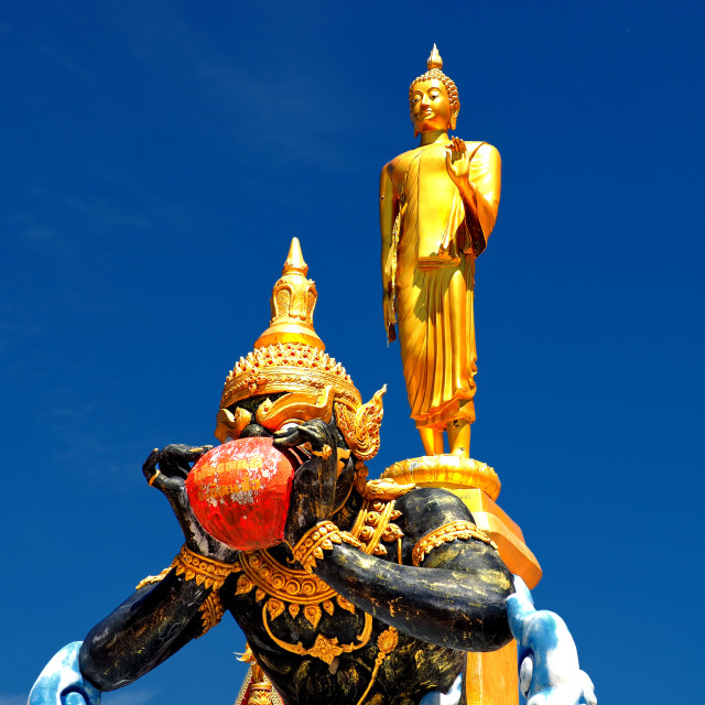 """Buddha and Phra Rahu soaring into blue sky"" stock image"