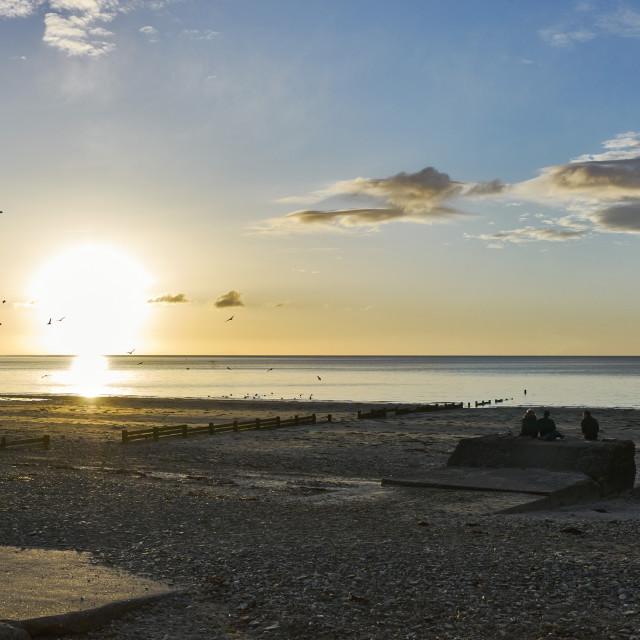 """Three people watching dawn break over sea and beach"" stock image"