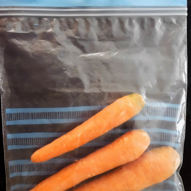 """""""Fresh Carrots in Plastic Storage Bag ready to be put in the Refrigerator"""" stock image"""