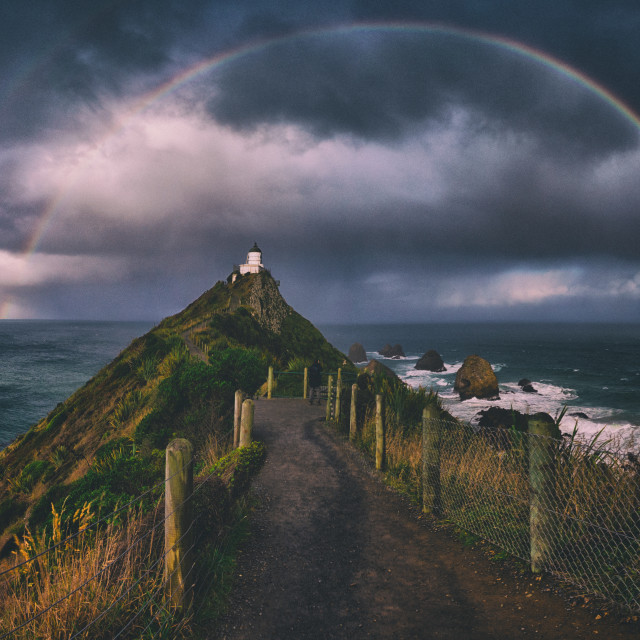 """Nugget Point Lighthouse, framed. This was my third time to this famous lighthouse in the Otago Region, New Zealand and it was the first time I'd managed to capture a rainbow framing the lighthouse. Rain was about to fall, and luckily I'd turn around t"" stock image"