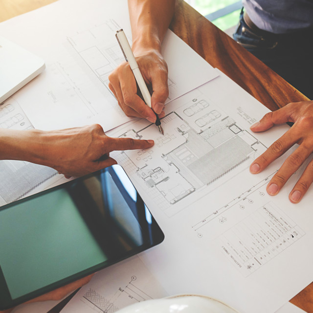 """Architects engineer discussing at the table with blueprint - Clo"" stock image"