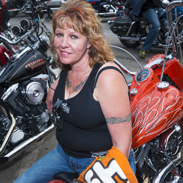"""""""Sturgis, South Dakota - August 8, 2014: Woman Rider sitting on her bike in the city of Sturgis, in South Dakota, USA, during the annual Sturgis Motorcycle Rally"""" stock image"""