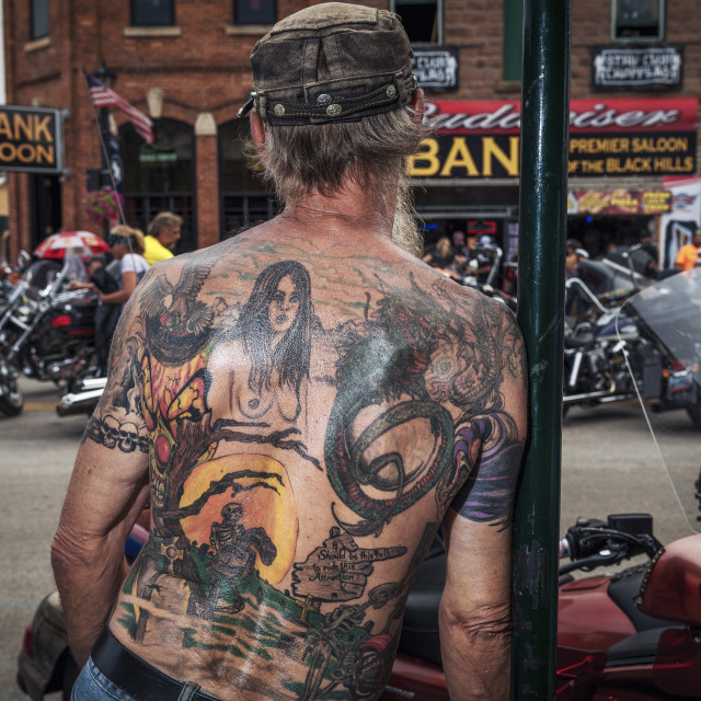 """Sturgis, South Dakota - August 8, 2014: Man with a tattoed back looking at the bikes in the city of Sturgis, South Dakota, USA, during the annual Sturgis Motorcycle Rally"" stock image"